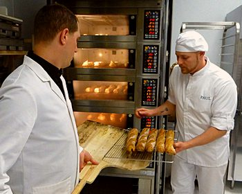 Thomas Crombez and Nicolas Gautier remove baguetts from oven at Masion Paul in Somerville