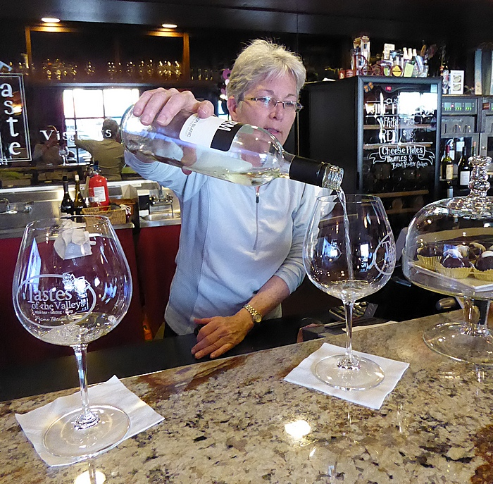 Lissa Hallberg of the Tastes of the Valleys purs a sample in Pismo Beach