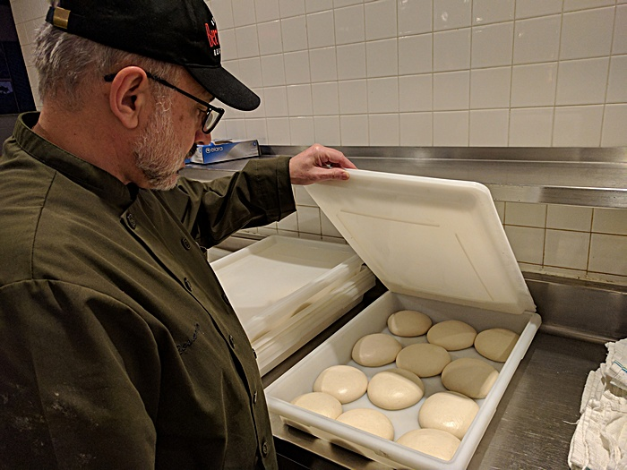Rosario Del Nero inspects pizza dough at Bertucci's