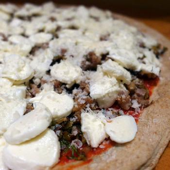 uncooked fennel and sausage pizza